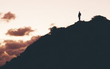 Hiker on Hill with Red Sky